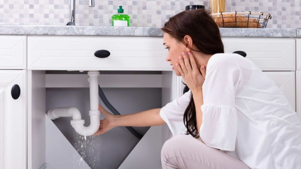 woman looking at kitchen sink leak, wondering whose insurance company will cover this repair