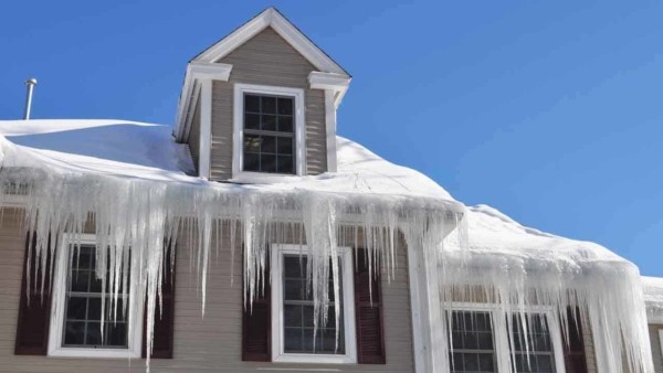 learn why ice dams form & how to prevent them so your house doesn't look like this one in Exeter, New Hampshire
