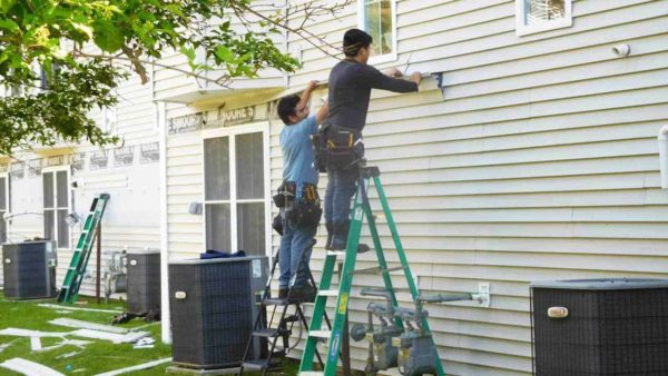 2 men replacing home vinyl siding ... working from ladders