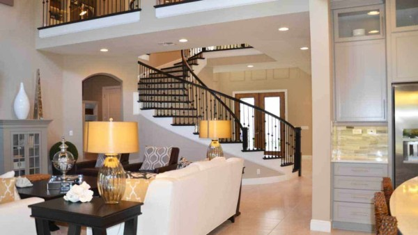 this open floor plan includes not only the kitchen and family room, it also opens up into the entryway and curving stairs plus the balcony above
