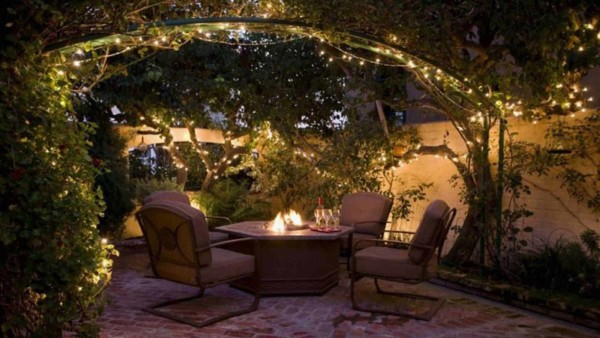 led fairy lights forming arbor over outdoor table and chairs
