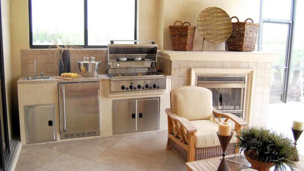 outdoor kitchens like this one with grill, refrigerator & fireplace, are among the most popular remodeling projects today