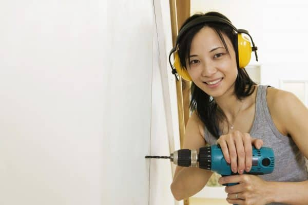 young woman with drill & headphones getting started on a home maintenance project