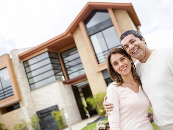 young couple smiling with their new house in the right home location