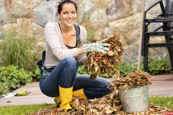 Young woman gathering leaves, something to look forward to at the end of your home buying journey