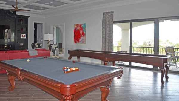 playroom with pool table & shuffleboard table mean this home entertainment room is a big hit