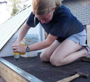 gabby installing drip edge on her tiny house