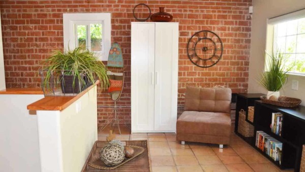 The interior of a great She Shed with brick walls and wide wood flooring.