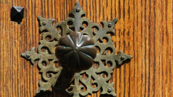 ornate antique door knob with delicate backplate behind it