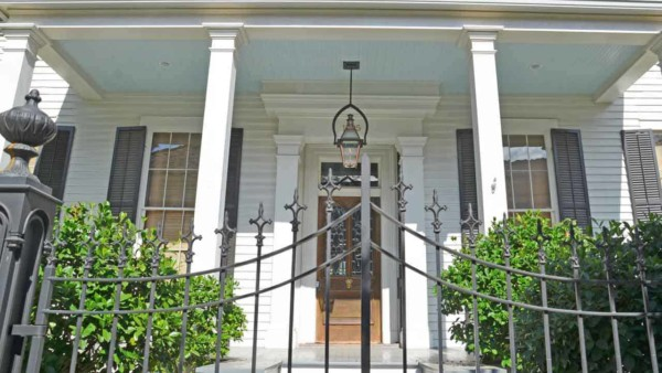 great curb appeal here from the arched fence to the lantern in front of a tall door with lots of decorative trim