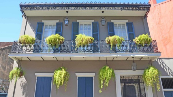 decorating with lanterns is very popular in New Orleans, from the street lights to porches & even balconies like this house has