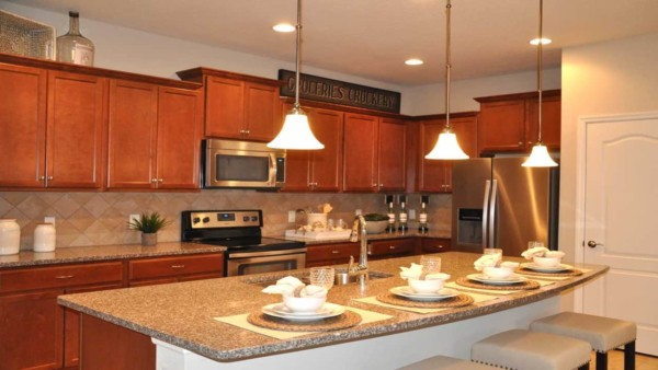 the red tones in this kitchen work well with the subtle red undertones in the tile backsplash