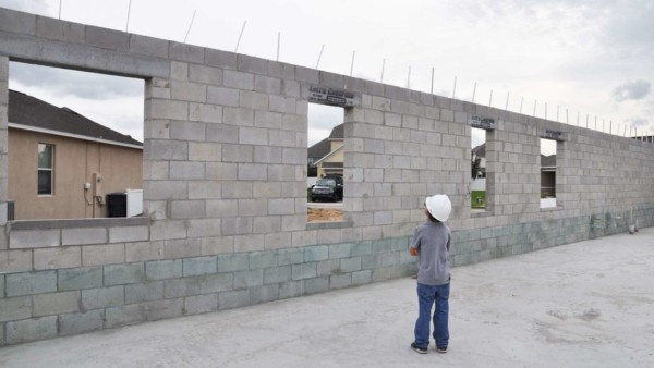 young boy inspecting block walls in home under construction