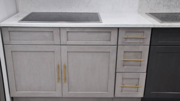 light gray kitchen cabinet with oversized gold pulls