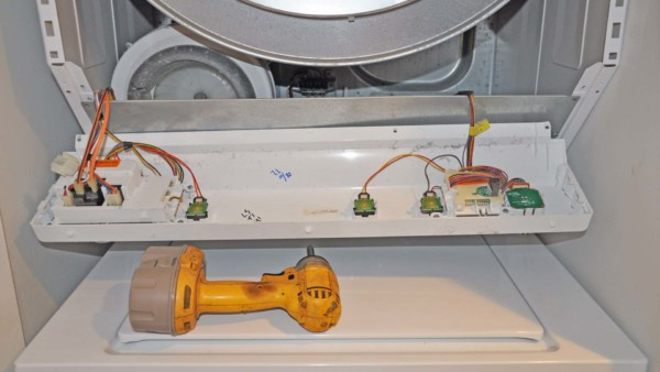appliance repair with dryer open to replace heating element