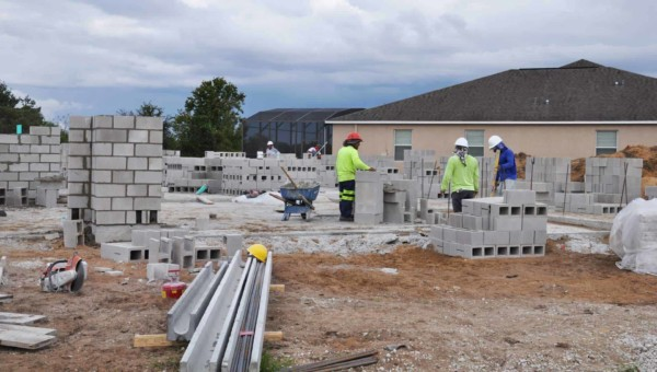 construction crew laying blocks forming exterior walls, things hidden during the process so they won't get onto the punchlist