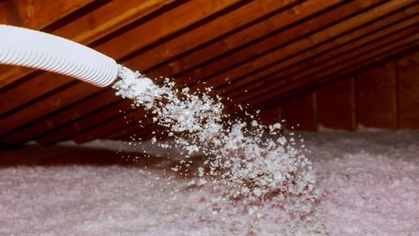 insulation being blown into attic floor cavities
