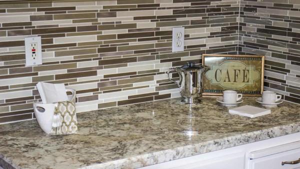 kitchen counter electrical outlets in tile backsplash over granite countertop