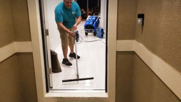 water mitigation company pushing water out the front door before talking to your insurance company