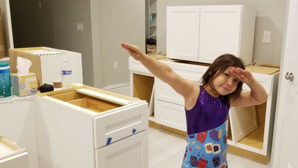 my granddaugher playing amid the chaos of cabinets, furniture & boxes scattered throughout the house