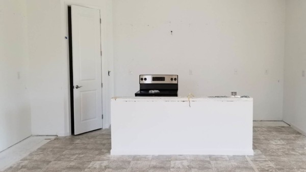 empty kitchen with island wall & stove after cabinets removed