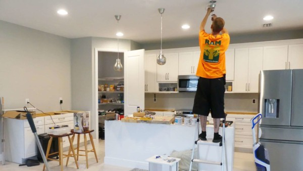 handyman installing kitchen island pendant lights over beautiful, not cheap kitchen cabinets