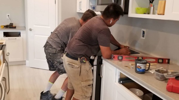 contractors moving stove back after installing counter tops over new cabinets, not original cheap kitchen cabinets