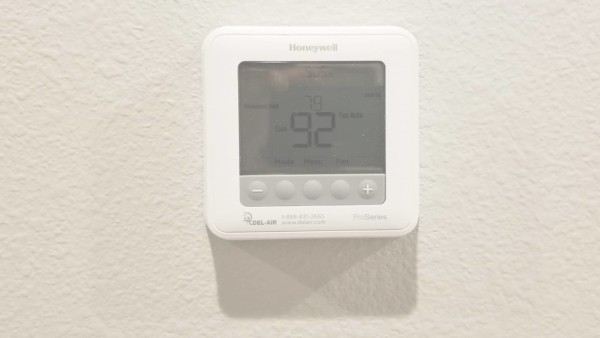 thermostat showing house temperature at 92 degrees, creating an environment for mold growth & why hiring a public adjuster was so important