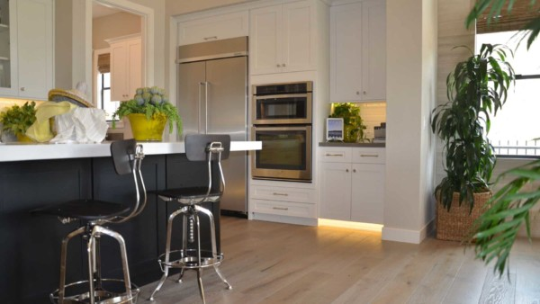 kitchen design trends shown here, white cabinets with an island of black cabinets