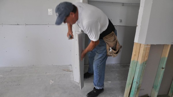 drywall installer screwing in replacement drywall after house flooded