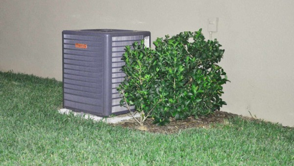 HVAC compressor hiding behind bushes that are too close & condensate line ends underneath the bush