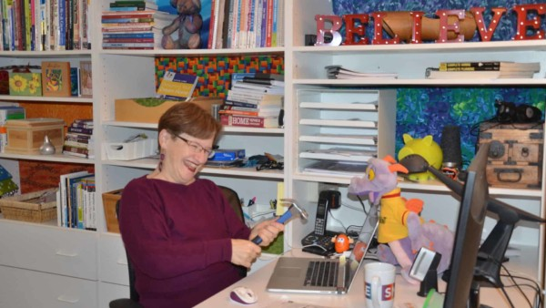 Tina Gleisner, founder of HomeTipsforWomen.com, surrounded by books on anything home, her laptop & lots of color