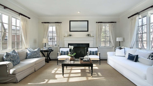 beautiful living room with white furniture & curtains; walls painted with cream matte paint fiish